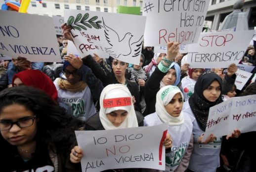 "A girl holds a placard during a protest called ""Not in my name"" of Italian muslims against terrorism, in downtown Milan"